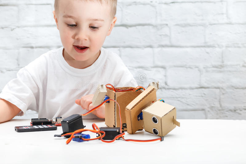 Little boy plays with the robot. Child collects a robot sitting at the table stock images