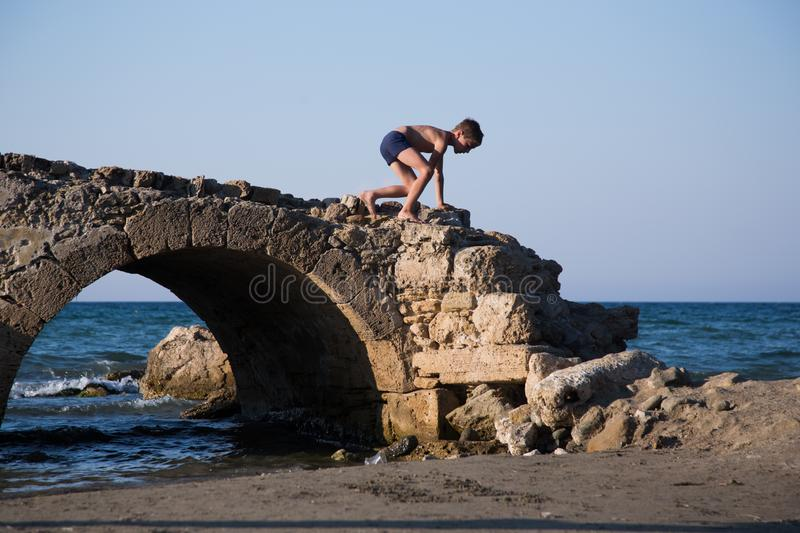 Little boy plays on a ruined old stone bridge next to a beach. stock photos