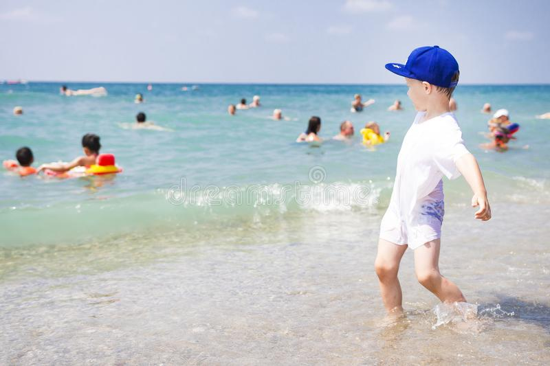 Little boy plays on sea beach. People swim and relaxing in warm water of sea. Sunny summer beach on tropical vacation stock photography