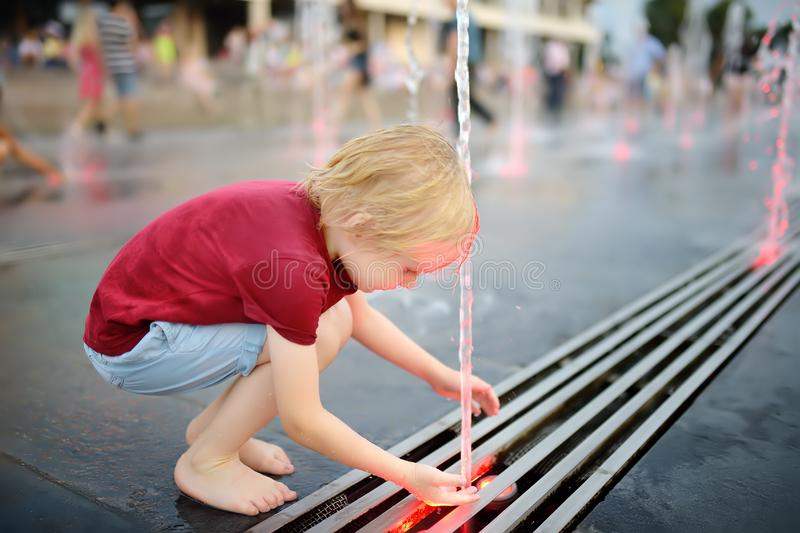 Little boy plays in the square between the water jets in the fountain at summer evening. Active summer leisure for kids in the city royalty free stock photography