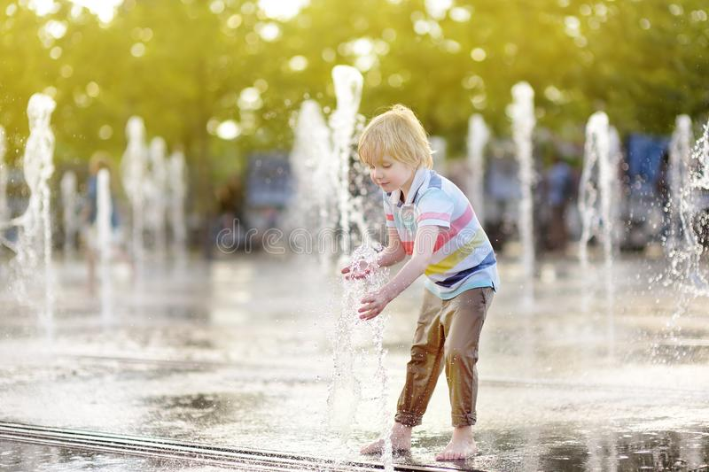 Little boy plays in the square between the water jets in the fountain at sunny summer day royalty free stock photography