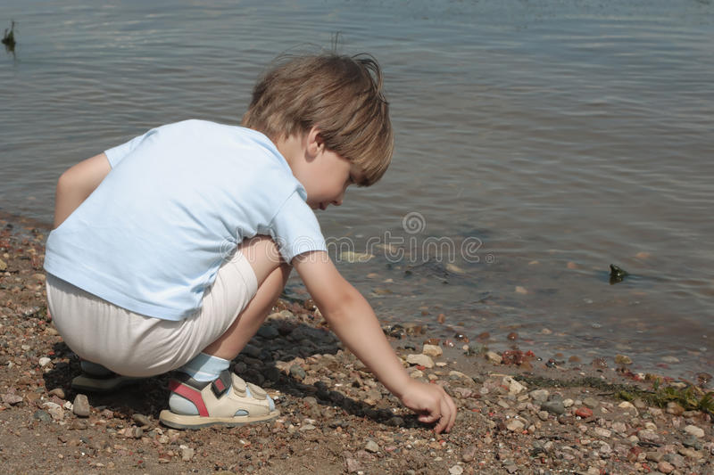 Download Little Boy Plays With Stones Stock Photo - Image: 25745932