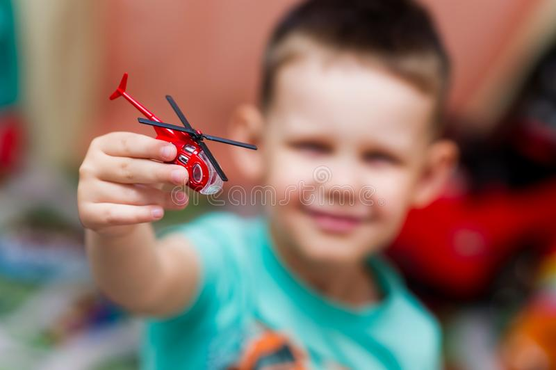 Boy playing with a toy red helicopter royalty free stock photo