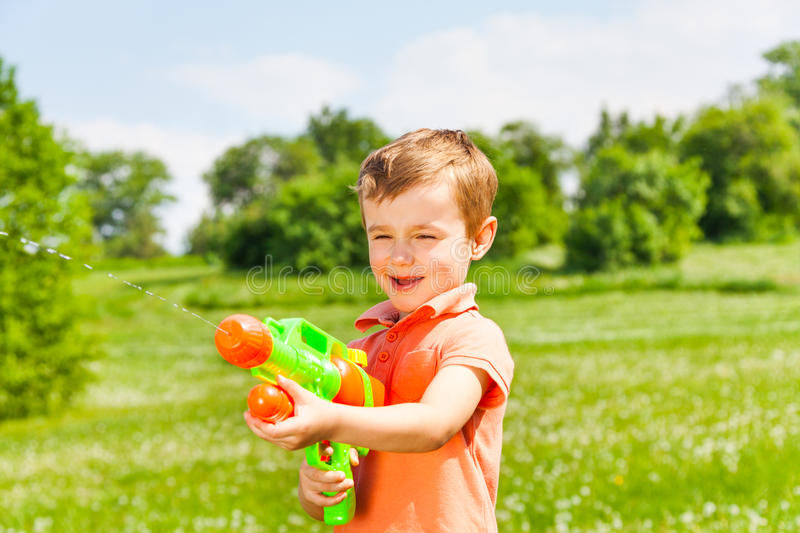 Little boy plays with a water gun. Little pretty boy plays with a water gun on a beautiful meadow royalty free stock photo