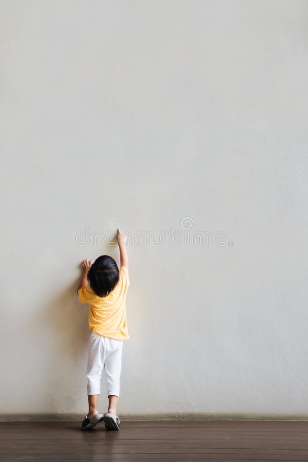 The little boy pointed at the blank white wall royalty free stock image