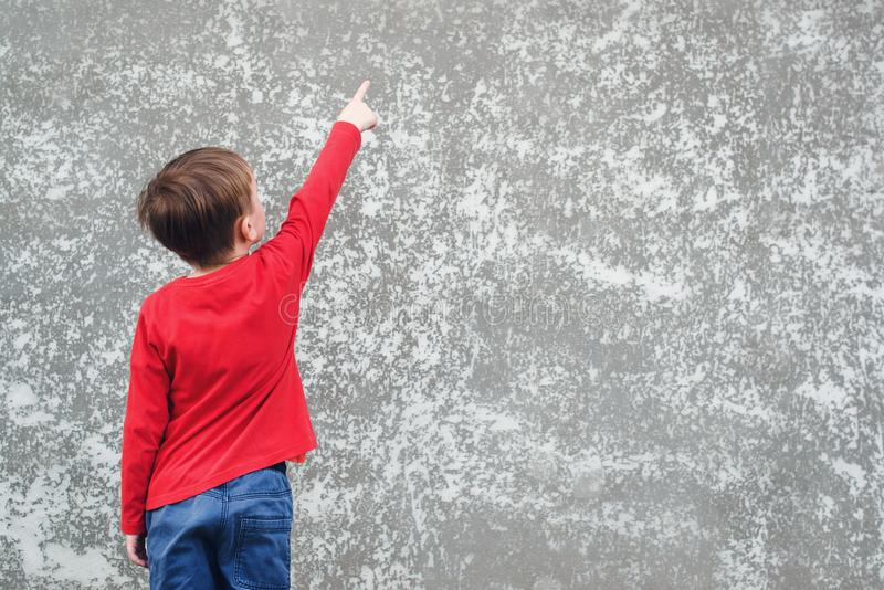 Little boy pointing on empty place at concrete wall. Back view of child. Cool boy wearing red shirt and jeans. Mockup. Child is royalty free stock image