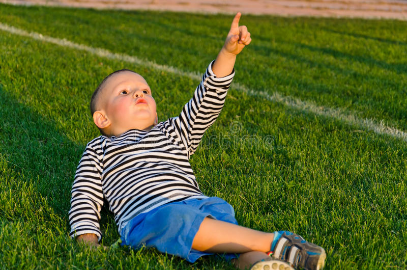 Little boy pointing up at the sky stock photo