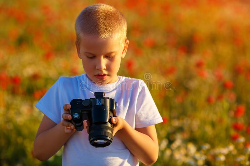 Little happy boy in poppy field at sunset with camera stock photography