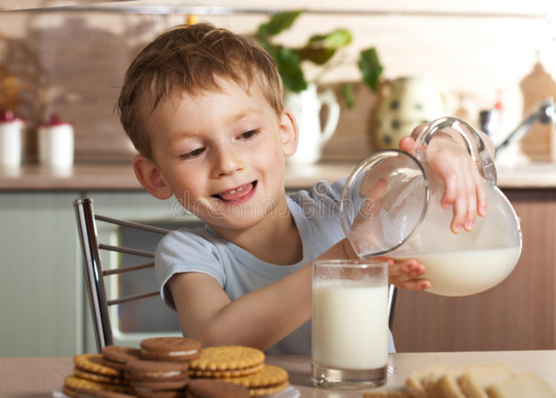 Download Little Boy Pours Milk From Jug Stock Image - Image: 9392285