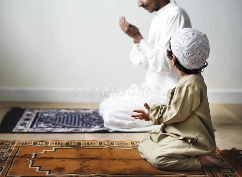 Little boy praying alongside his father during Ramadan stock photo