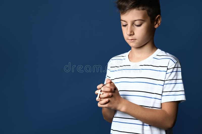 Little boy praying on color background royalty free stock images