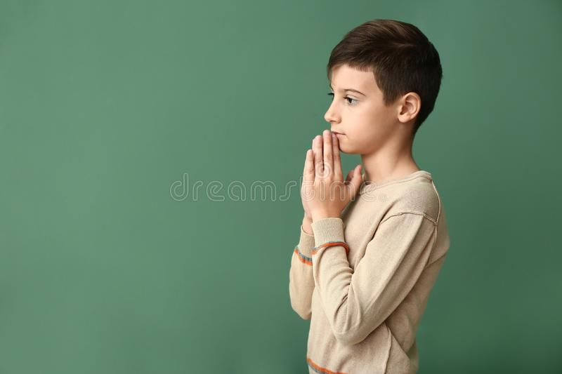 Little boy praying on color background stock images