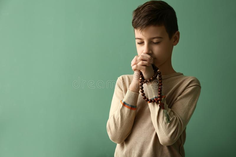 Little boy praying on color background royalty free stock image