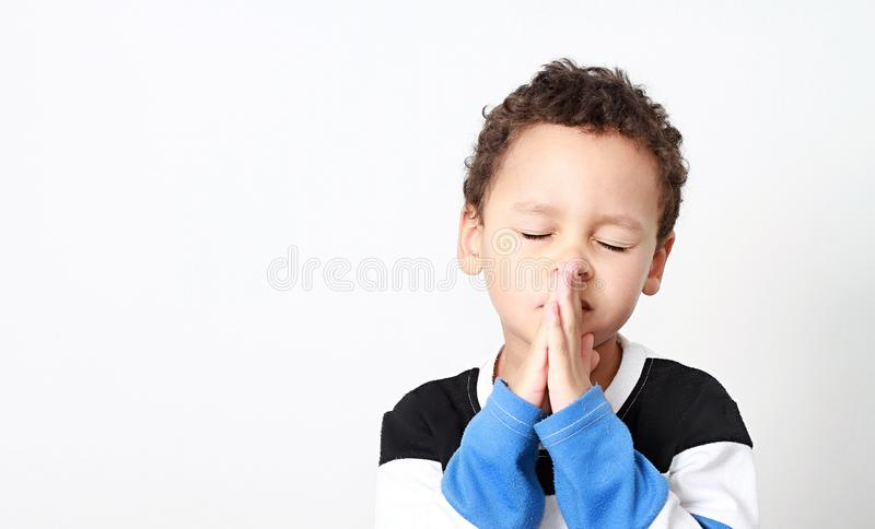 Little boy praying with his hands clenched together stock images