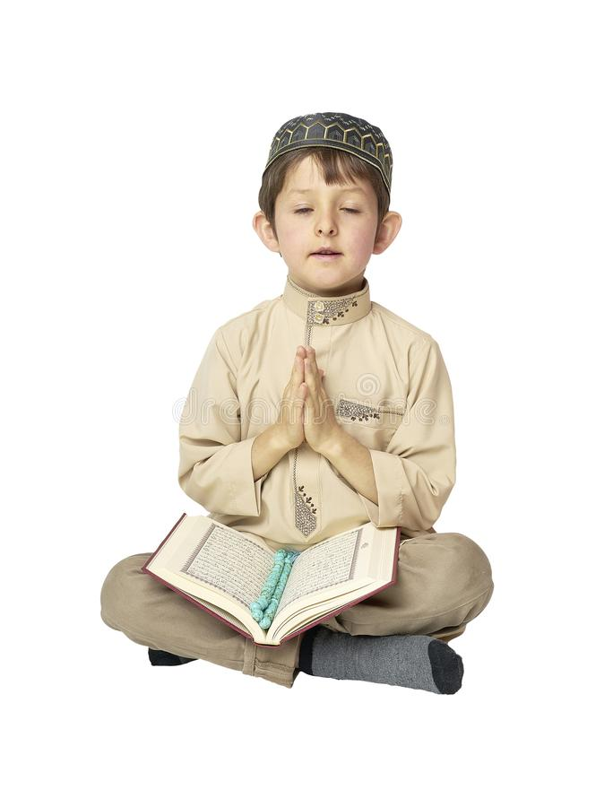 Little boy praying and holding Koran with rosary beads on white background. Muslim Arabic boy praying on white background royalty free stock photos