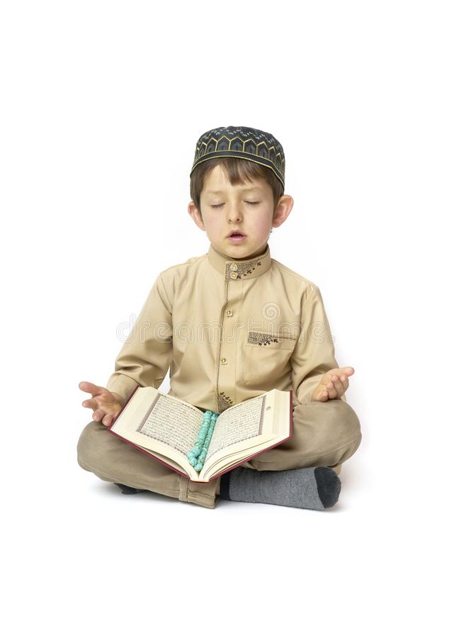 Little boy praying and holding Koran with rosary beads on white background. Muslim Arabic boy praying on white background stock photography