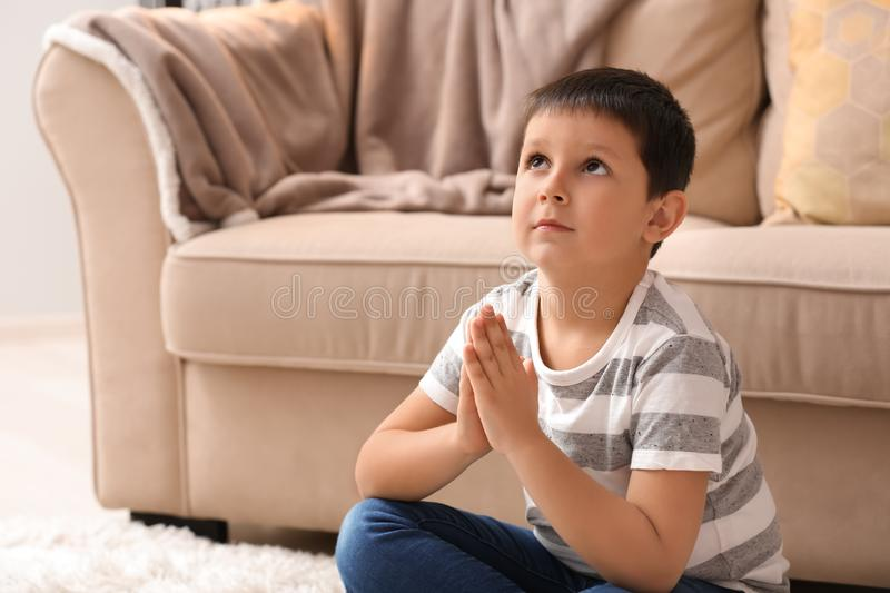 Little boy praying at home stock images