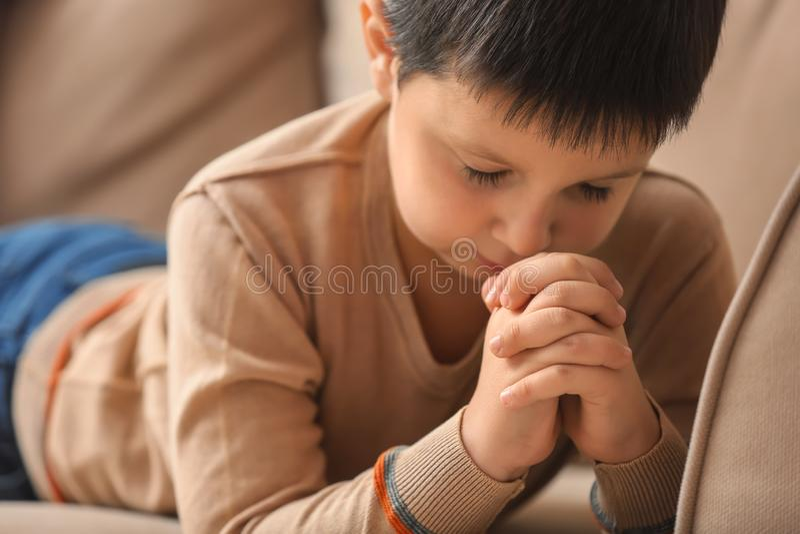 Little boy praying at home stock image