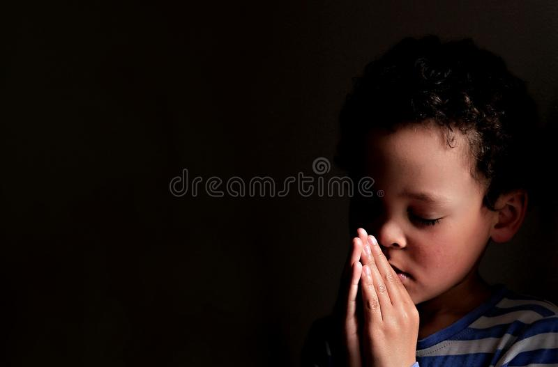 Little boy praying to God with hands held together stock photo stock photo