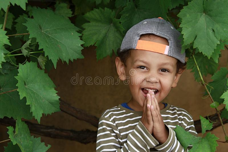 Little boy praying to God with hands held together stock photo. Little boy praying to God with hands held together and head held high with a smile on his face royalty free stock images