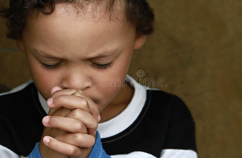 Little boy praying to God with hands held together stock photo. Little boy praying to God with hands held together and head held high with a smile on his face royalty free stock photos