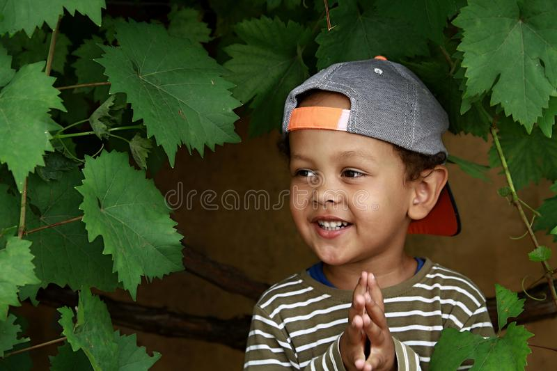 Little boy praying to God with hands held together stock photo. Little boy praying to God with hands held together and head held high with a smile on his face royalty free stock photography