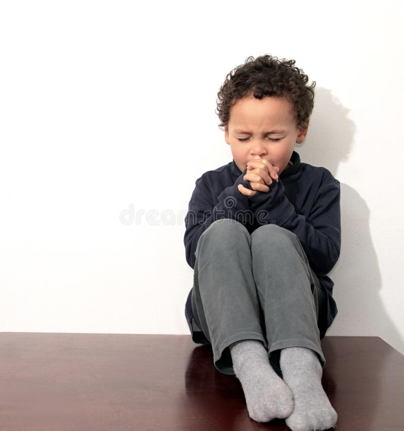Little boy praying to God with hands held together royalty free stock images