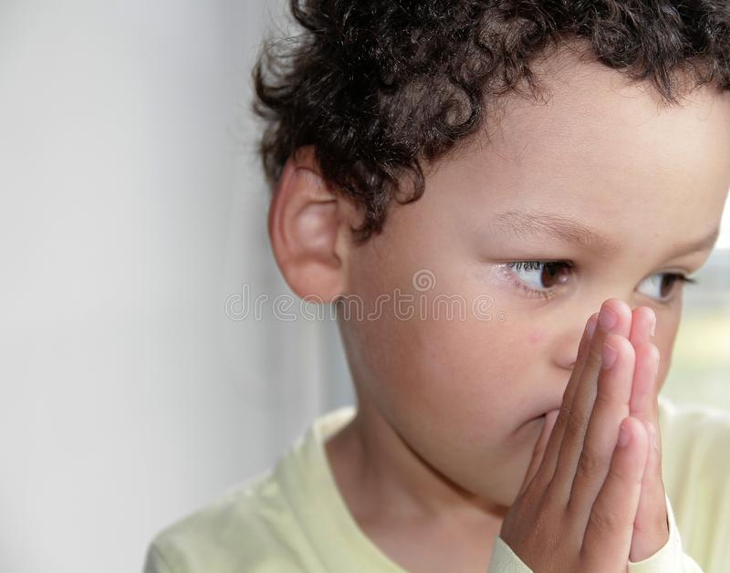 Little boy praying to God with hands held together stock photo stock image