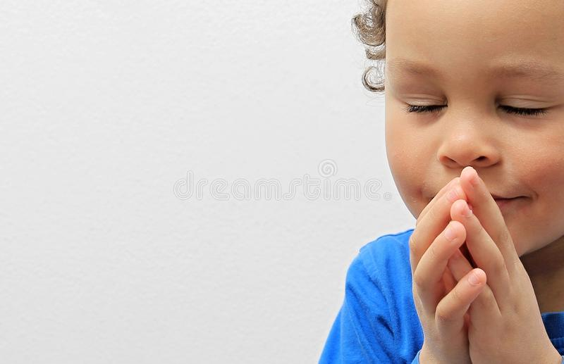 Little boy praying to God with hands held together stock photo royalty free stock photo