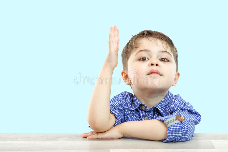 Little boy of preschool age raises his hand to answer the question or ask the question. on an  background.  stock images