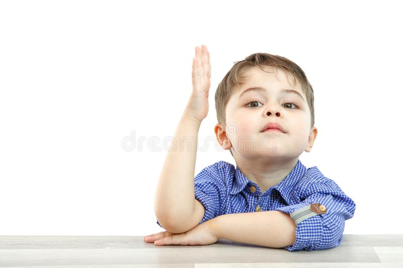 Little boy of preschool age raises his hand to answer the question or ask the question. on an isolated background.  stock photos