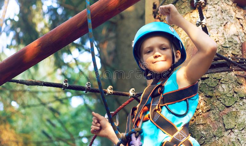 Little boy in a protective helmet and in special equipment passes an obstacle course at height. Little Caucasian boy in a protective helmet and in special royalty free stock photography