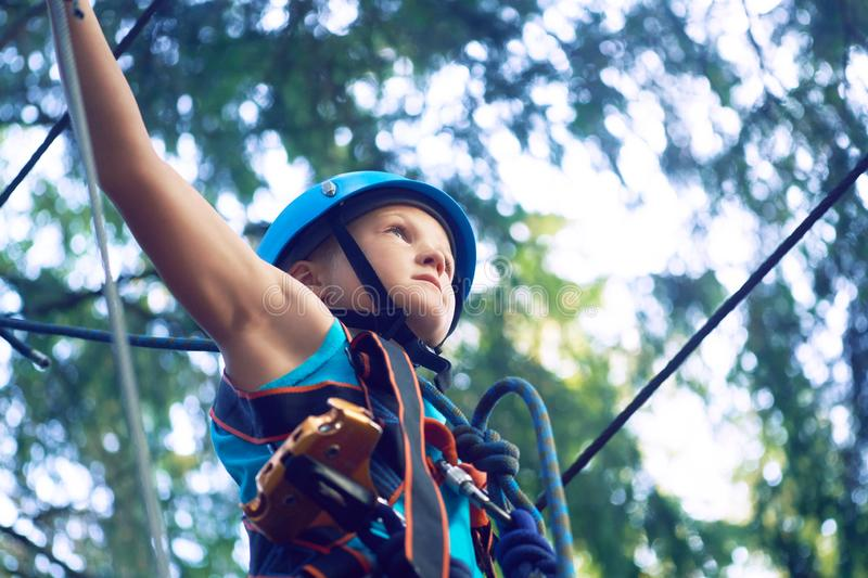Little boy in a protective helmet and in special equipment passes an obstacle course at height. Little Caucasian boy in a protective helmet and in special stock photo