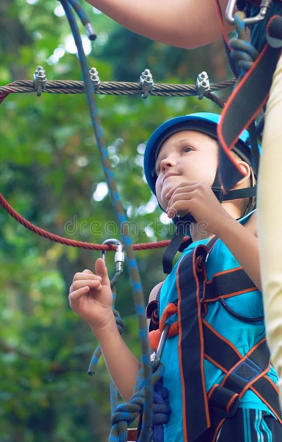 Little boy in a protective helmet and in special equipment passes an obstacle course at height. Little Caucasian boy in a protective helmet and in special stock photos