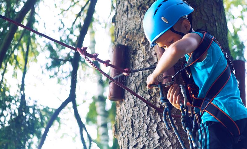 Little boy in a protective helmet and in special equipment passes an obstacle course at height. Little Caucasian boy in a protective helmet and in special royalty free stock images