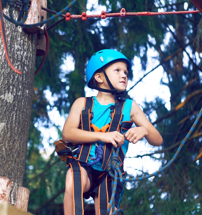 Little boy in a protective helmet and in special equipment passes an obstacle course at height. Little Caucasian boy in a protective helmet and in special royalty free stock photo