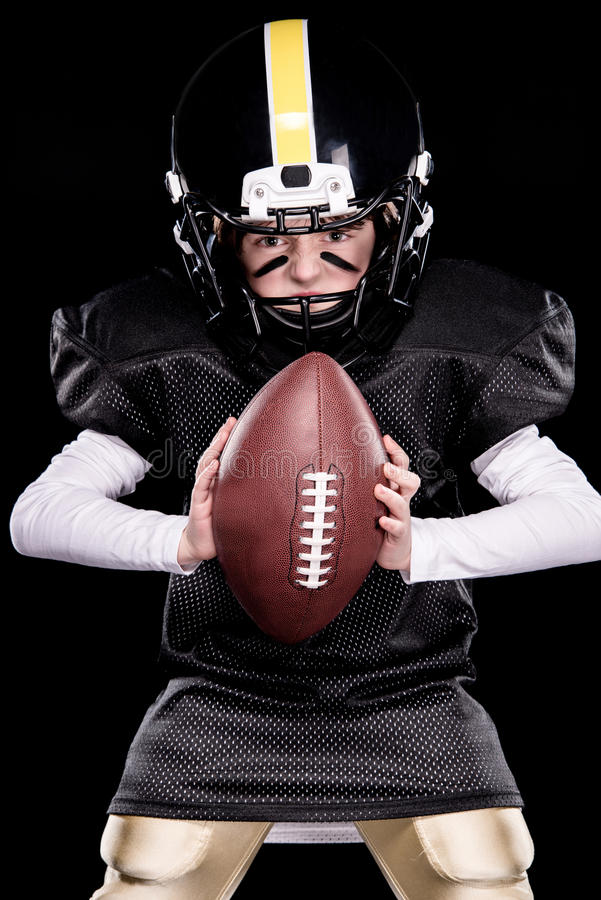 Little boy in protective sportswear playing american football with ball stock photos