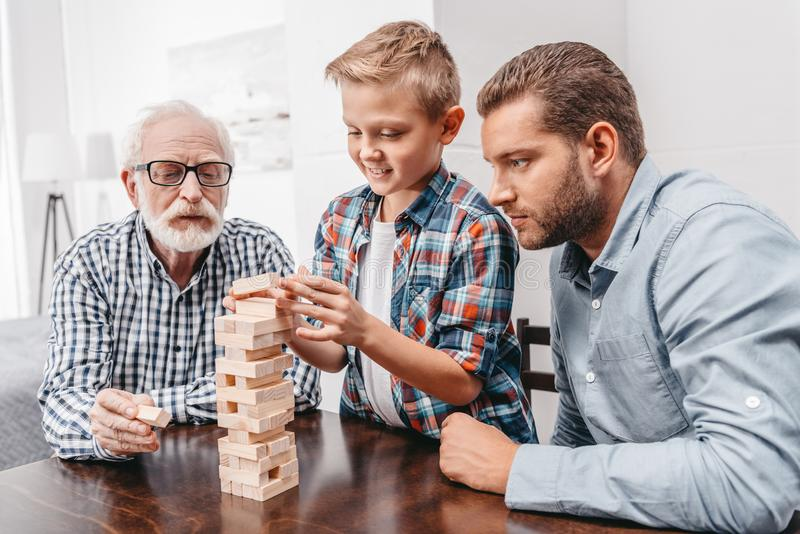 Little boy pulling a piece out of blocks wood tower while his father and grandfather stock photo