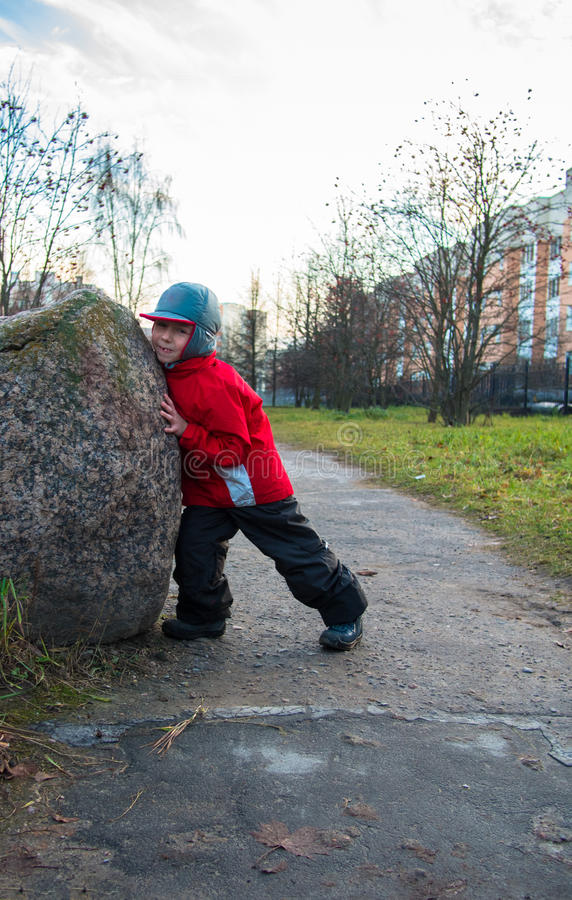 Little boy pushes a large rock royalty free stock photo