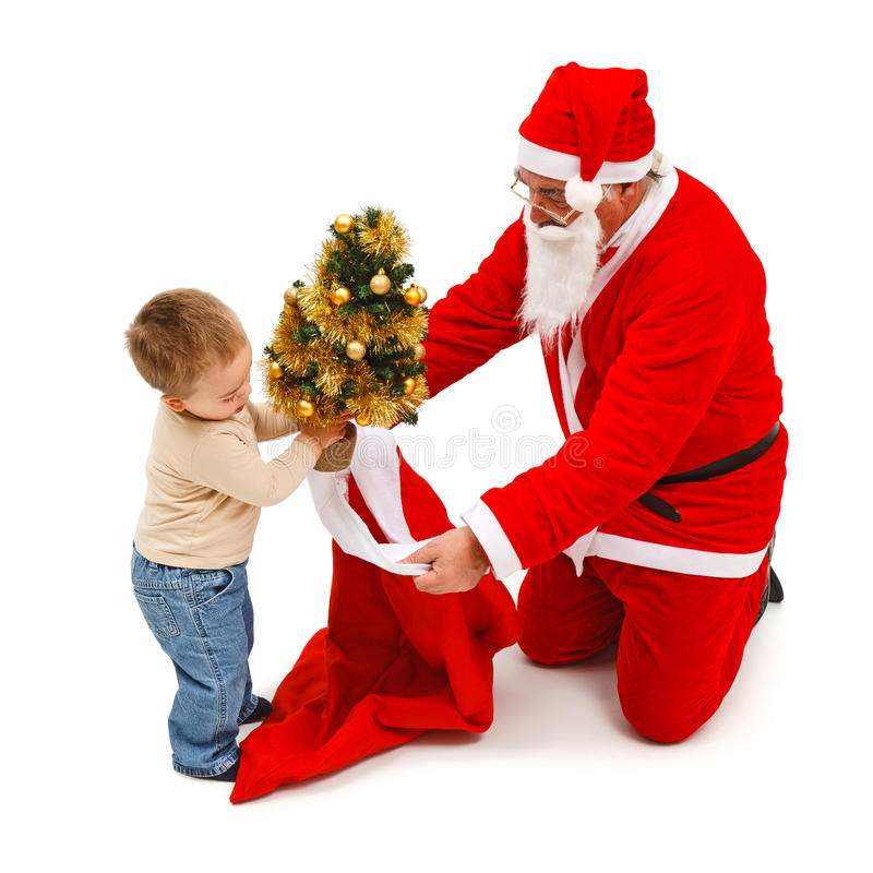 Little boy puts small tree in Santa's bag stock photos