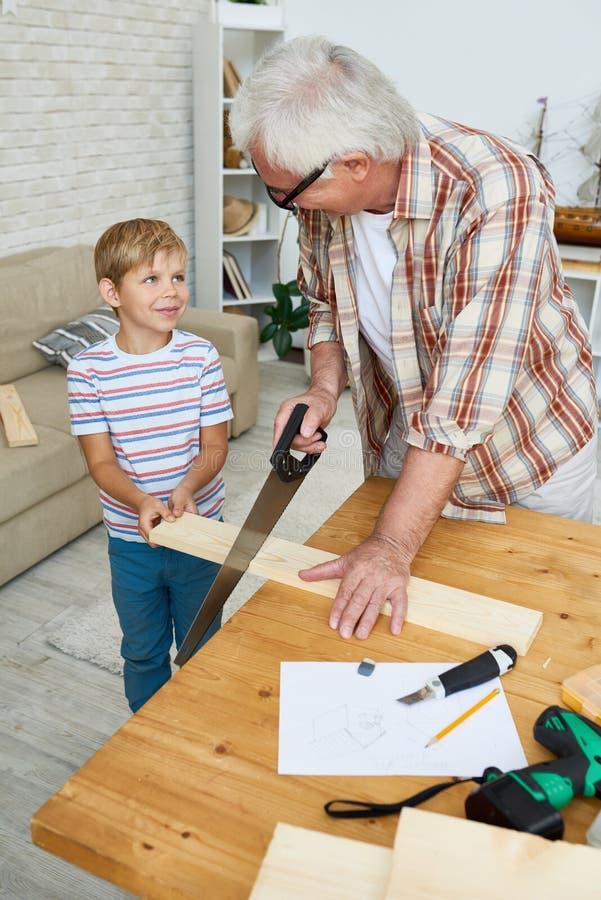 Little Boy que ajuda o carpinteiro superior imagem de stock royalty free