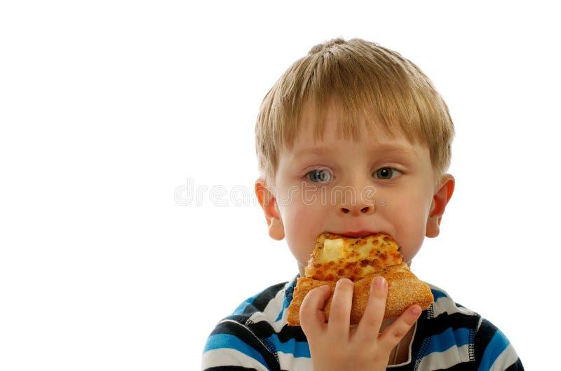 Little Boy que come a pizza imagens de stock