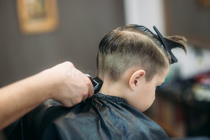 Little Boy que consigue corte de pelo de Barber While Sitting In Chair en la barbería fotos de archivo