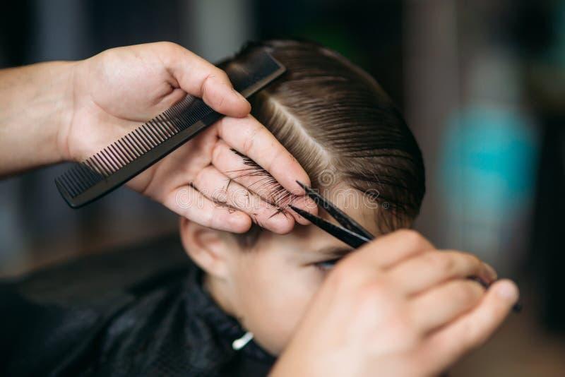Little Boy que consigue corte de pelo de Barber While Sitting In Chair en la barbería  imagenes de archivo