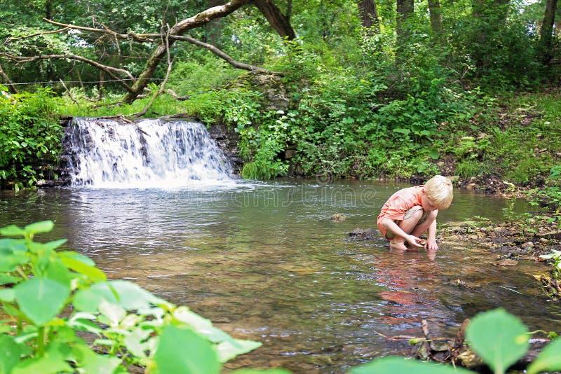 Little Boy que explora en la naturaleza que busca rocas en el río imágenes de archivo libres de regalías