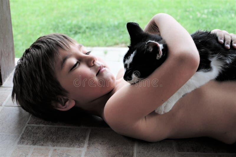 Little Boy que guarda o gato foto de stock