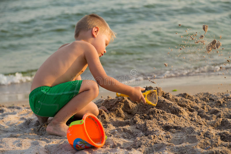 Little Boy que joga com a areia na praia foto de stock royalty free