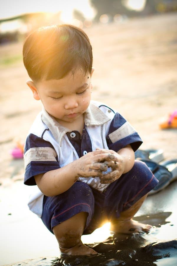 Little Boy que joga na lama imagem de stock