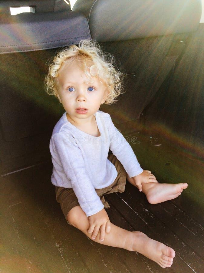 Little Boy que se sienta en un coche foto de archivo libre de regalías