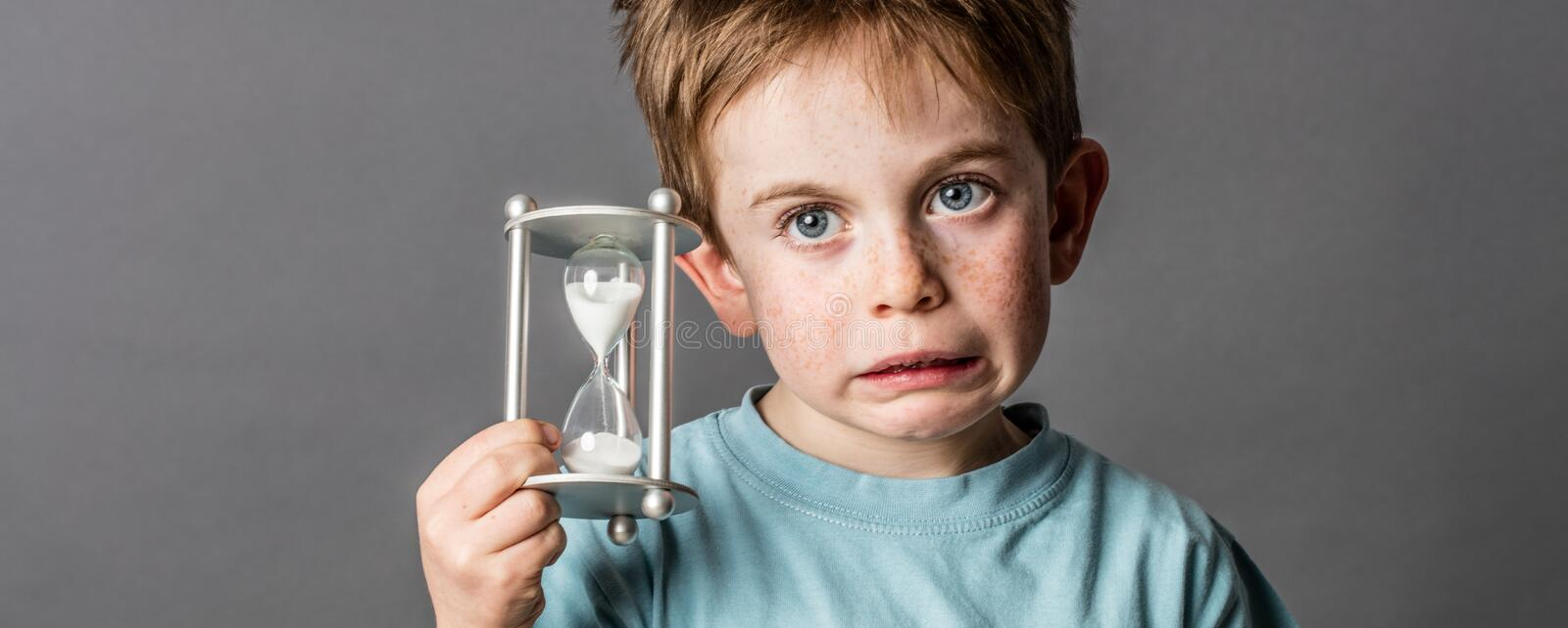 Little boy with questioning eyes holding a scary egg timer royalty free stock photo